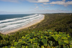 Coastline. Beutifull coastline and wave hitting the beach. Green landscape at the distance. Byron Bay - Australia stock photography