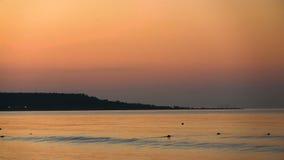 Coastline against the background of the orange dawn. Sea Calm. stock video