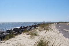 Beautiful Coastline along Mobile Bay in Alabama USA. The coastline along mobile bay is shown with a rock barrier, sand and sea oats and an asphalt road which royalty free stock photo