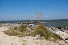 Beautiful Coastline along Mobile Bay in Alabama USA. The coastline along mobile bay is shown with a rock barrier, sand and sea oats which curves around Historic Stock Images