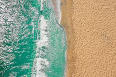 Coastline Beach Ocean waves with foam on the sand. Top view from drone stock image