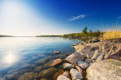 Coastline with boulders and trees. Coastline with boulders and evergreen trees - Sunny day in may, Sweden Stock Photo