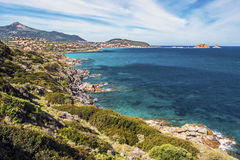 Coastline in east of Ile-Rousse in Corsica. Coastline landscape in approach Ile-Rousse city in Corsica Island, seen at background with Pietra islet at right Royalty Free Stock Images