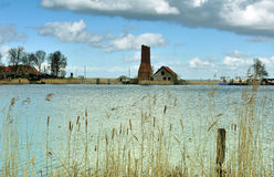Coastline at Enkhuizen in  Ijsselmeer. Pier of ferry boat and lime kiln at  open air museum in Enkhuizen, Netherlands Stock Image