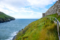 Coastline with green grass and great wall of Peel Castle in Peel, Isle of Man Stock Images
