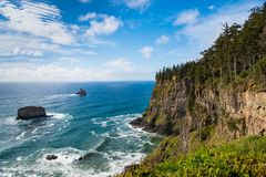 A coastline of high, green forested cliffs with a beautiful blue sea and sky stock photo