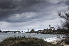 Coastline landscape in low tide with lighthouse and peculiar roc Royalty Free Stock Image