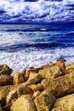 Coastline landscape - rocks, waves and cloudy sky Stock Photography