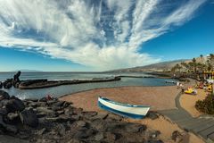 Coastline in Las Americas, Tenerife, Spain. Bright lue sky with beautiful clouds. Fishing boat in the foreground. La Gomera Island stock image