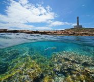 Coastline with a lighthouse and rocky seabed with fish underwater. Split view half above and below water surface, Mediterranean sea, Cabo de Palos, Cartagena stock photo