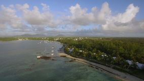 Coastline of Mauritius, aerial view. Aerial shot of Mauritius landscape. Coast with villas and palms alongside, many yachts and boat in blue lagoon. Summer stock footage