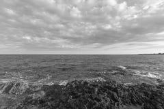 Coastline Mediterranean Sea in italy - monochrome. Beautiful cloudscape over the sea, rock sea Stock Photos