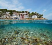 Coastline Mediterranean village Spain over under. Coastline of Mediterranean village on Costa Brava in Spain with sea bass fish and rocks underwater, Sa Tuna stock images