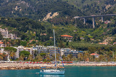 Coastline of Menton - town on French Riviera. White yacht on background of Menton coastline - small town and touristic resort on French Riviera Stock Photography