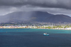 Coastline in the mist along a Saint Kitts and Nevis island in Ca. Ribbean sea Stock Image