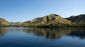 Coastline of mountains with green vegetation reflected  in blue ocean water at Labuan Bajo in Flores. Royalty Free Stock Photos