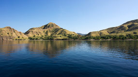 Coastline of mountains with green vegetation reflected  in blue ocean water at Labuan Bajo in Flores. Stock Photo