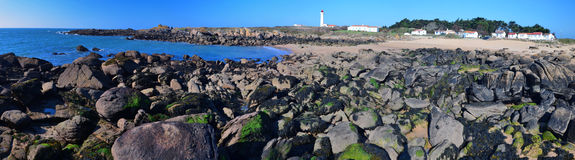 Coastline Panorama of at Pointe des Corbeaux of Yeu Island. Coastline stones in the east of Yeu island surrounded with sand, the lighthouse of Pointe des Stock Photo