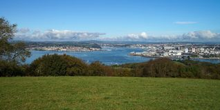 Coastline of Plymouth in United Kingdom. Green grass in the front. Blue cloudy sky at background stock photography