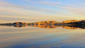 Coastline & reflections along Otago Peninsula lake Stock Photo
