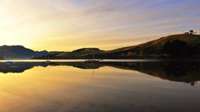 Coastline & reflections along Otago Peninsula lake Stock Images