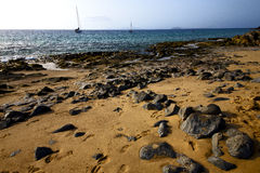Coastline rock beach  water boat yacht Stock Images