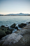 Coastline rocks in satin soft atlantic ocean, mountain trois couronnes at sunset in long exposure, basque country, france Royalty Free Stock Images
