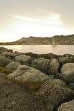 Coastline rocks in satin soft atlantic ocean, sailing boat and mountain jaizkibel at sunset in long exposure Royalty Free Stock Images
