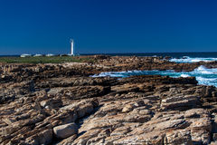Coastline Rocks White Lighthouse. White light house at the edge of a large rocky dangerous coastal area for the fishing and ships safety on the east coast of Stock Photos