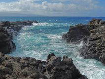 Coastline and rugged lava rocks called Dragon's Teeth and crashing waves at Makaluapuna Point near Kapalua, Maui, HI, USA. Coastline and rugged lava rocks Royalty Free Stock Photo