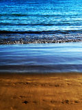 Coastline Sand View. Water waves washing up onto the sandy beach Royalty Free Stock Images