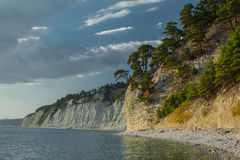 The coastline on the sea coast, with a high cliff above it Royalty Free Stock Photo