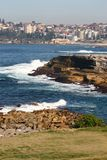 Idyllic and amazing seaside landscape of jagged shore with rocks, white rushing sea waves, hillside buildings in Sydney, Australia royalty free stock photo