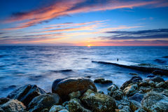 The coastline with stones in the water at sunset Stock Photos