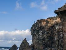 Coastline (Tenerife - Canary Island). Rough coast - man fishing - blue sky - clouds Royalty Free Stock Photo