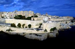 Coastline traditional architecture in Valletta,Malta. Siege Bell - World War II Memorial and traditional stone made buildings in Valletta,Malta with coastline Royalty Free Stock Image