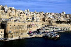 Coastline traditional architecture in Valletta,Malta. Traditional stone made buildings in ancient city Valletta,Malta with coastline,fishing ships and blue sky Royalty Free Stock Image