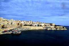 Coastline traditional architecture in Valletta,Malta. Traditional stone made buildings in ancient city Valletta,Malta with coastline,fishing ships and blue sky Royalty Free Stock Photos