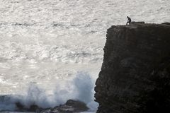 Lonely man on cliff. Coastline view of a lonely man on top of cliff gazing the ocean Royalty Free Stock Photos
