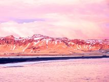 Coastline view at Dyrholaey in Iceland. Coastline view with mountains near Dyrholaey, Vik town in Iceland, during twilight evening sky in winter season royalty free stock images