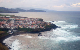Coastline village Maia above the Atlantic ocean, Azores islands. Beautiful picturesque small coastal village houses on the rocky lava shore above the Atlantic Royalty Free Stock Image