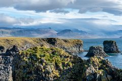 View of the west coastline in Iceland. The coastline at the west part of Iceland with lava rock formations and mountain peaks royalty free stock photo