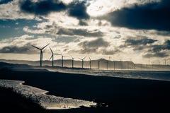 在海洋coastt的风轮机剪影在日落 菲律宾 免版税库存图片