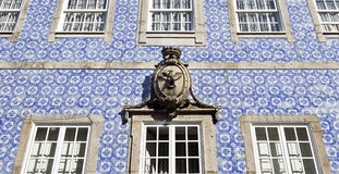 Coat of Arms and Building Facade. Detail of a coat of arms placed above the central window on the decorative facade of a main building in Braga, Portugal Stock Photos