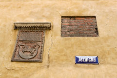 Coat of arms, fragment of brick wall in Warsaw. Coat of arms, fragment of brick wall and street name plate on Jezuicka street in Old town of Warsaw, Poland Stock Photos