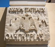Coat of arms and Greek religious symbol,cross,plaque with name on wall of  monastery in Crete, Greece Stock Image
