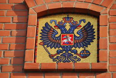 The coat of arms in the Kremlin wall. The coat of arms of Russia in the Kremlin wall - the two-headed eagle with St. George on horseback Stock Image