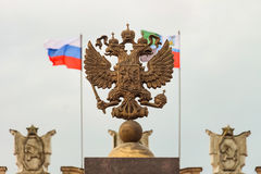 Coat of arms Russia. N Federation. Coat of arms on background of parapet administrative building government with USSR symbols, flags of Russia and Belgorod Stock Photo