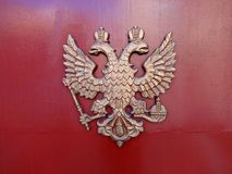 Coat of arms of the Russian Federation with double-headed eagle. On a red metal background royalty free stock photography