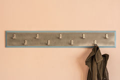 Coat hanger and coat. Photographed hanger for clothes on the wall Stock Photos